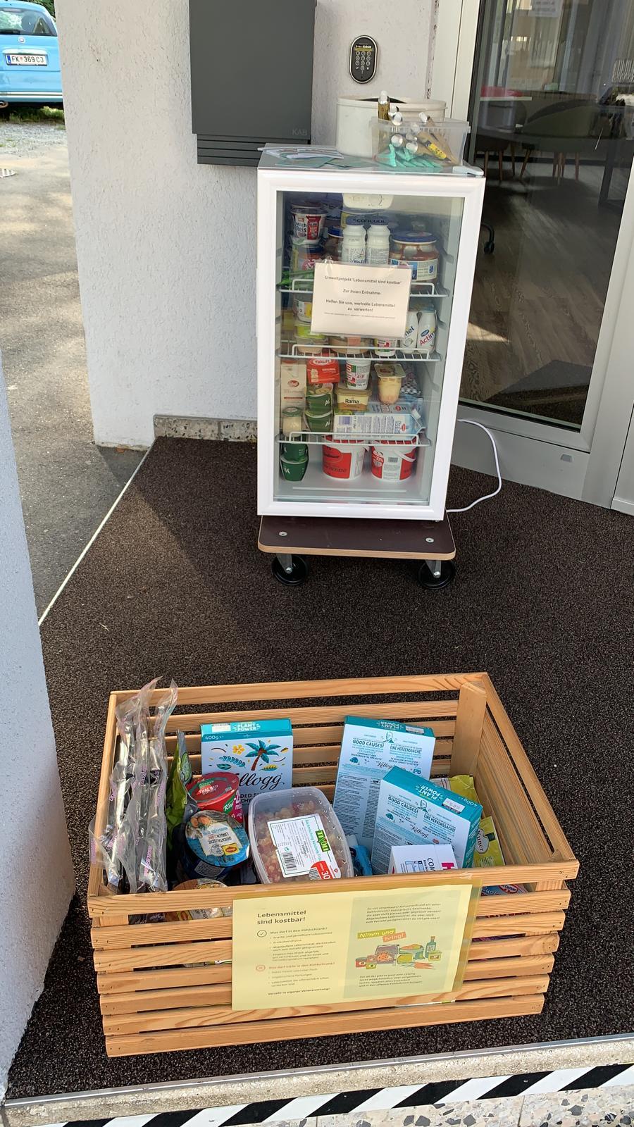 Foto offener Kühlschrank und Holzkiste mit Lebensmitteln